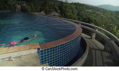 Young girl is swimming in pool atop a mountain stock footage...