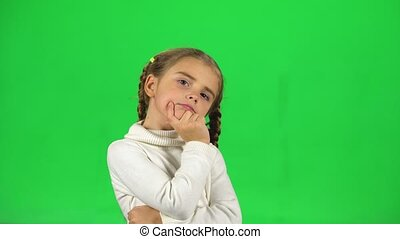 Young girl is thinking in studio on green screen