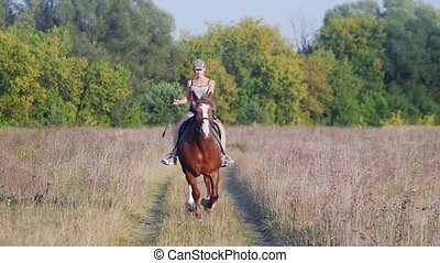 Young girl jockey in a baseball cap riding a horse on the...