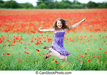 Young girl jumping for joy in a field of red poppies as she...