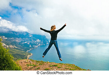 young girl jumping on the mountain