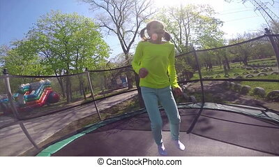 Young girl jumping on  trampoline.