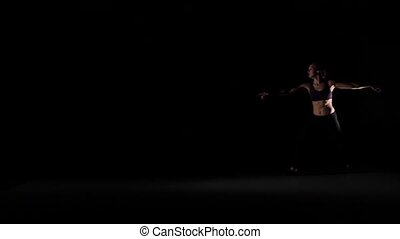 Young girl jumps dancing contemp in the shadow on black background, slow motion