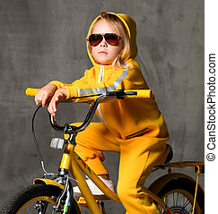 Young girl kid ride sit on yellow bicycle in sunglasses looking up on grey concrete wall