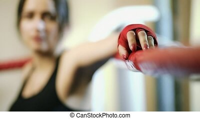 Young girl, latino woman has put her hand on the ring rope, only hand is in focus.