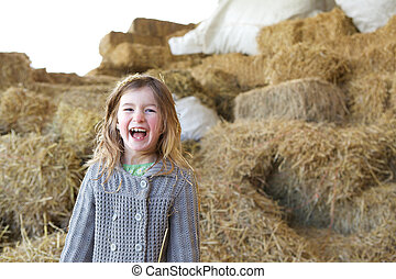 Young girl laughing on farm