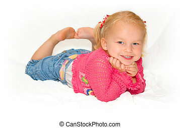 Young girl laying on a sheet, smiling