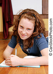 young girl laying on the floor writing - a young female...
