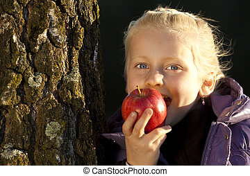 Young girl leans on tree and bite in an appel