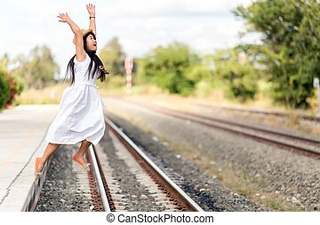 Young girl leaping off a train station platform