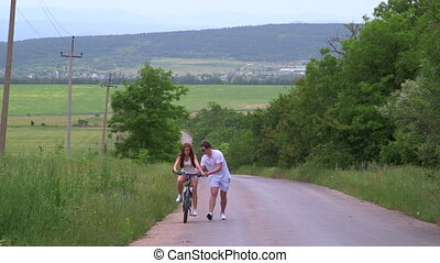 Young girl learning to ride bicycle on a country road