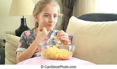 Young girl likes potato chip