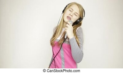 young girl listening music on headphones holding microphone, singing and funy dancing