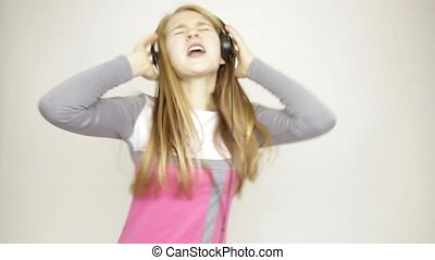 young girl listening music on headphones, singing and funy dancing