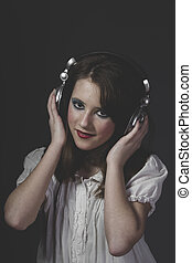 young girl listening music with huge headphones