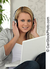 Young girl listening to her laptop on headphones