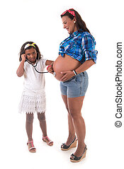 young girl listening to her pregnant mother belly