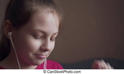 Young girl listening to music from earings and feeling rhythm.