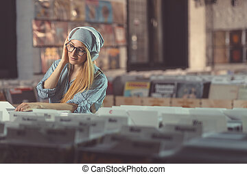 Young girl listening to music in music store