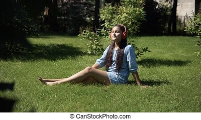 Young girl listening to music on headphones sitting on grass in park in sunny weather. 4K