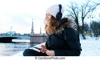 Young girl listens to music outdoors in the winter, sings the song and dances sitting on the snow