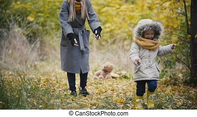 Young girl - little daughter laughs and plays catch-up with the mother in autumn park, slow motion