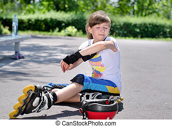 Young girl sitting on the tarmac at the skate park looking at her bruised arm after taking a fall on her rollerblades