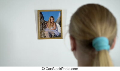 Young girl looking at photograph of a little girl in photo frame on the wall