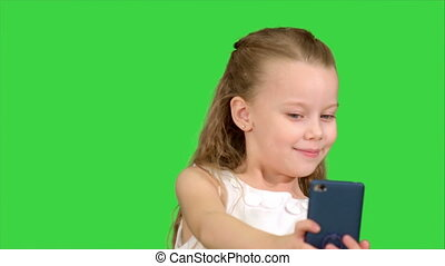 Young girl looking into the camera smiling taking selfie on a Green Screen, Chroma Key