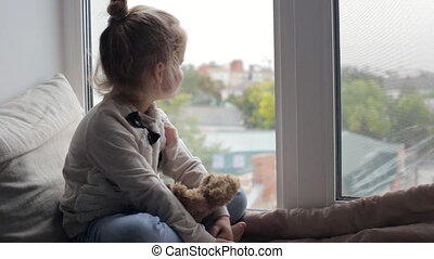 Young girl looking out the window sitting on window sill