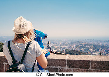 Young girl looking through a coin operated binoculars on the Barcelona