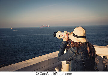 Young girl looking through a coin operated binoculars on the sea