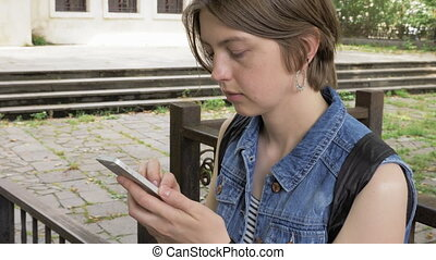 Young girl looks at the smartphone in the park