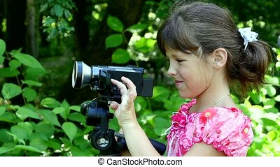 Young girl looks into video camera on background of green park slow motion.