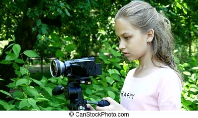 Young girl looks into video camera on background of green park background.