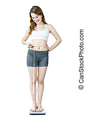Young girl losing weight - Happy fit young woman measuring...