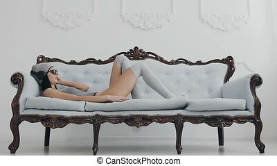 Young girl lying on a beautiful sofa relaxing and listening...