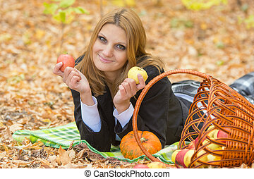 Young girl lying on a rug in the autumn forest and holding two apples in the hands of