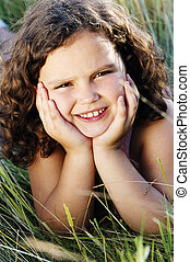 Young girl lying outdoors smiling
