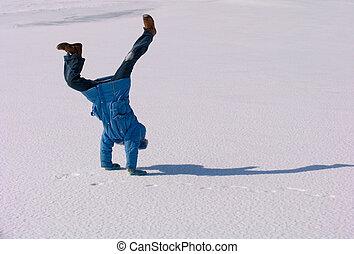 Cartwheel on the snow - Young girl making Cartwheel on the...