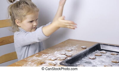 Young girl making handmade heart shaped cookies at home