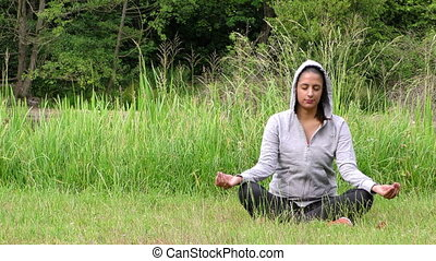 Young girl meditate in nature on grass