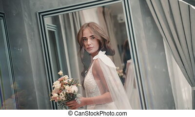 Young girl model demonstrates white wedding dress while standing in light room. Beautiful caucasian woman posing and moving her body, holding bouquet of flowers in hand at modern interior. Pretty lady looks at camera and poses for bridal photo shoot. Concept: person, beauty, luxury style.