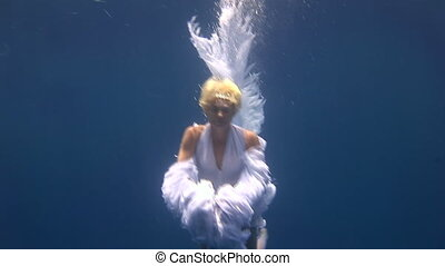 Young girl model free diver underwater white angel costume poses in Red Sea.