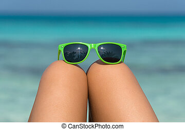 Young girl on a beach with glasses in legs