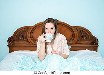 Young girl on a wooden in bed in the bedroom with a bowl in her hands