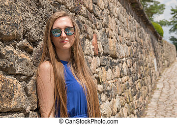 Young girl on background of old wall with door