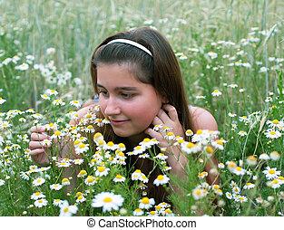 Young girl on chamomiles