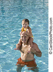 Young girl on father shoulders in swimming pool