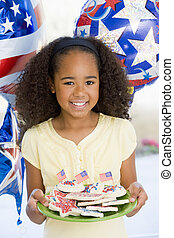 Young girl on fourth of July with balloons and cookies...